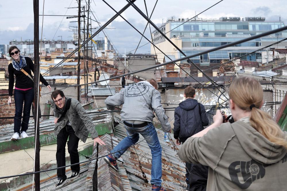 Fünf Studenten klettern über ein Dach von St. Petersburg.